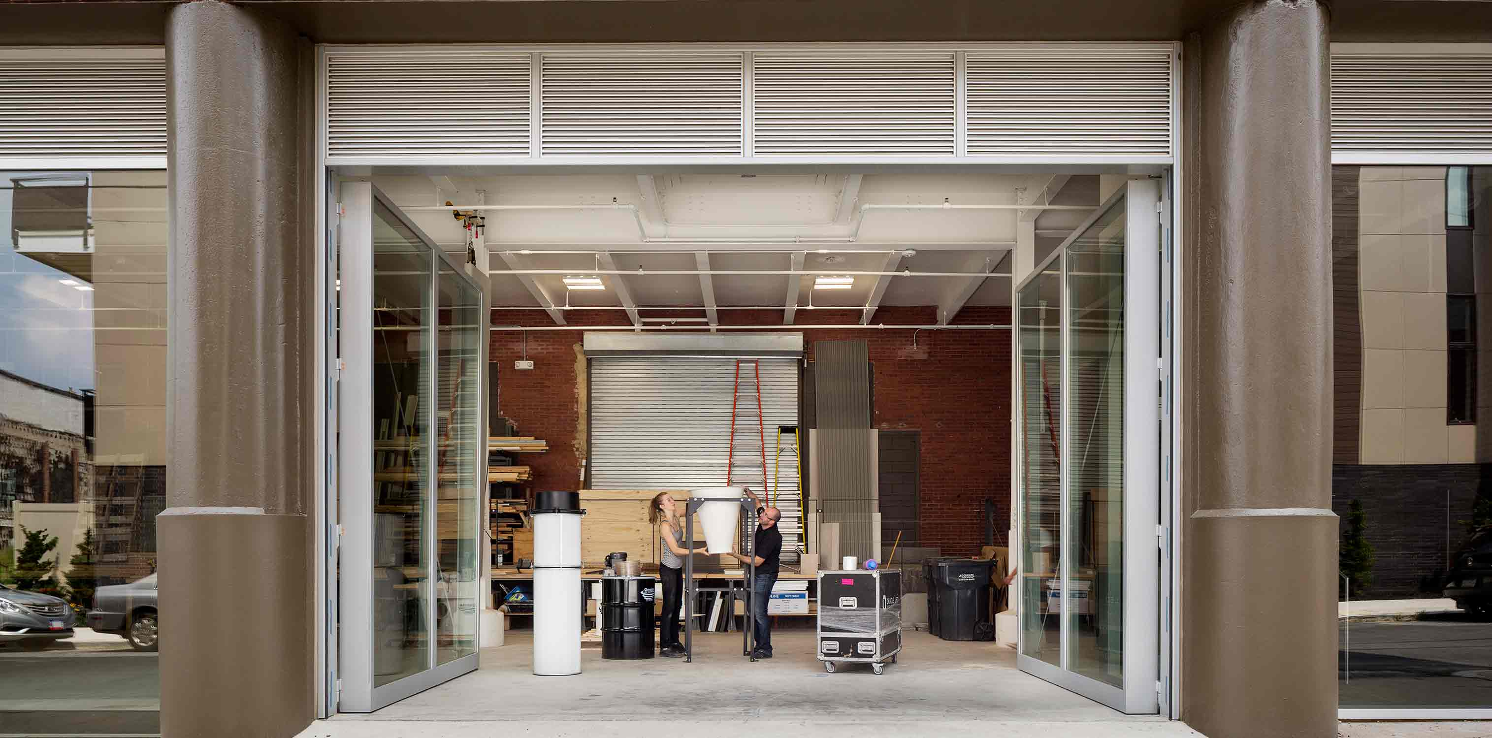 <p>The workshop's glass doors measure 13 feet high and open onto the street to provide natural ventilation and to allow for the movement of full-scale building mockups.<br> <br /><small>©Michael Moran</small></p>
