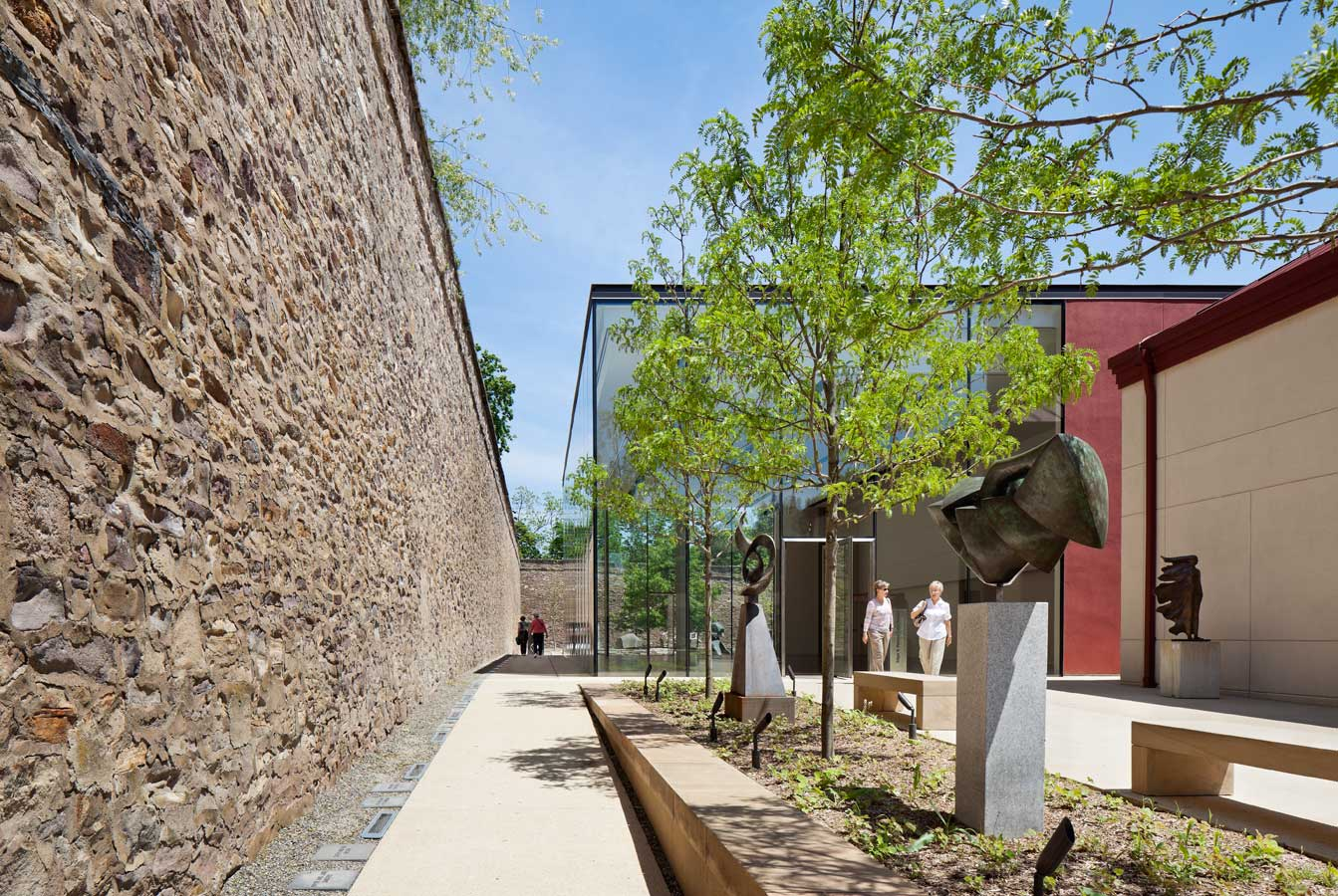 <p>The stone wall of the former prison appears to enter the space through the uninterrupted glass walls of the pavilion, lending visual interest and historical reference to the structure. <br><small>&copy; Michael Moran/OTTO</small></p>