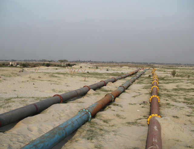 Development practices include sandfilling, a process that erases the deltaic ecology and alters the natural hydrology. In this photo, sand pipelines stretch across the land.