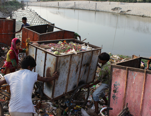 Workers dump trash from a rickshaw for use as landfill.