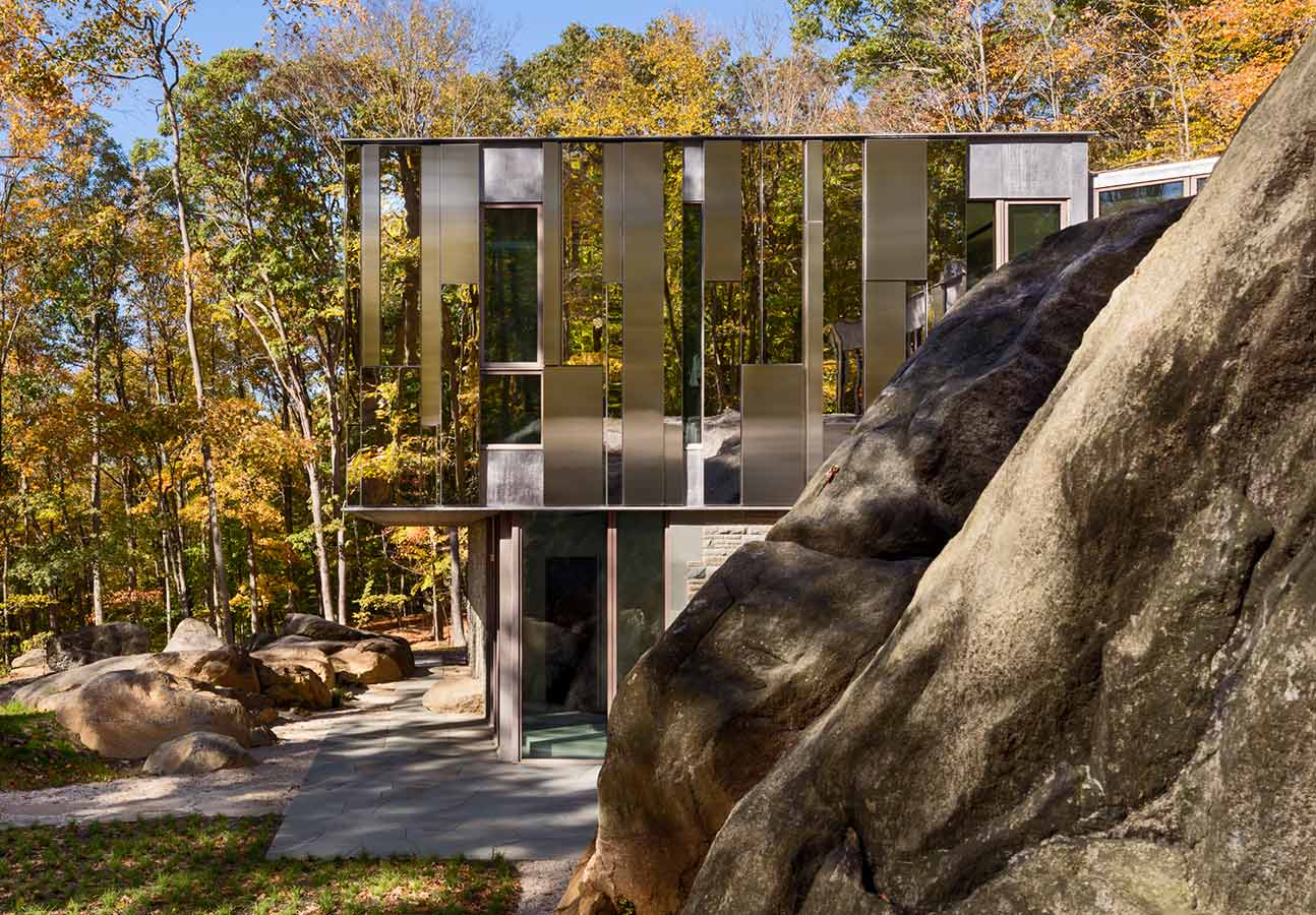 <p>As the home spatially amplifies the power of physical passage across the terrain, so too do its walls expand and magnify the presence of the spectacular granite outcroppings mingled with the forest. <br><small>© Peter Aaron</small></p>