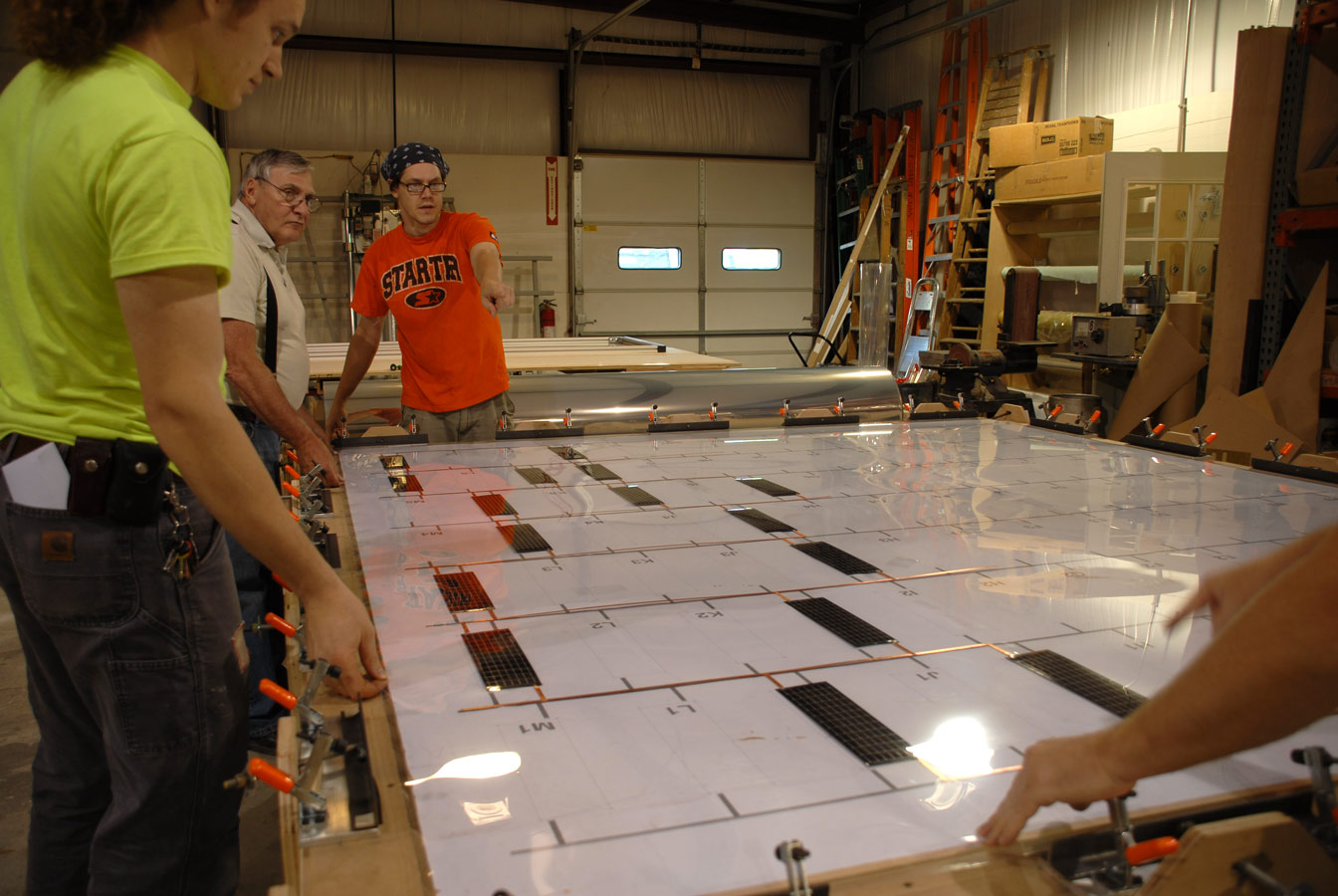 <p>The fabricator, Universal Services Associates, Inc., built a custom table to stretch the PET to achieve the best balance of tension and stability for the frames. The table included a template to guide the placement of thin-film PVs.</p>