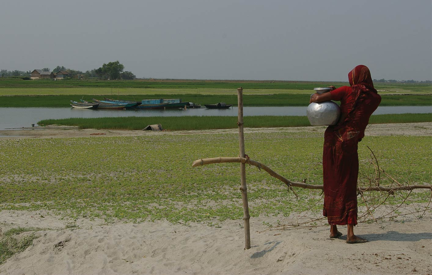 <p>A woman carrying water stands before a shallow waterway separating char settlements. There are typically no roads or formal access to chars.</p>