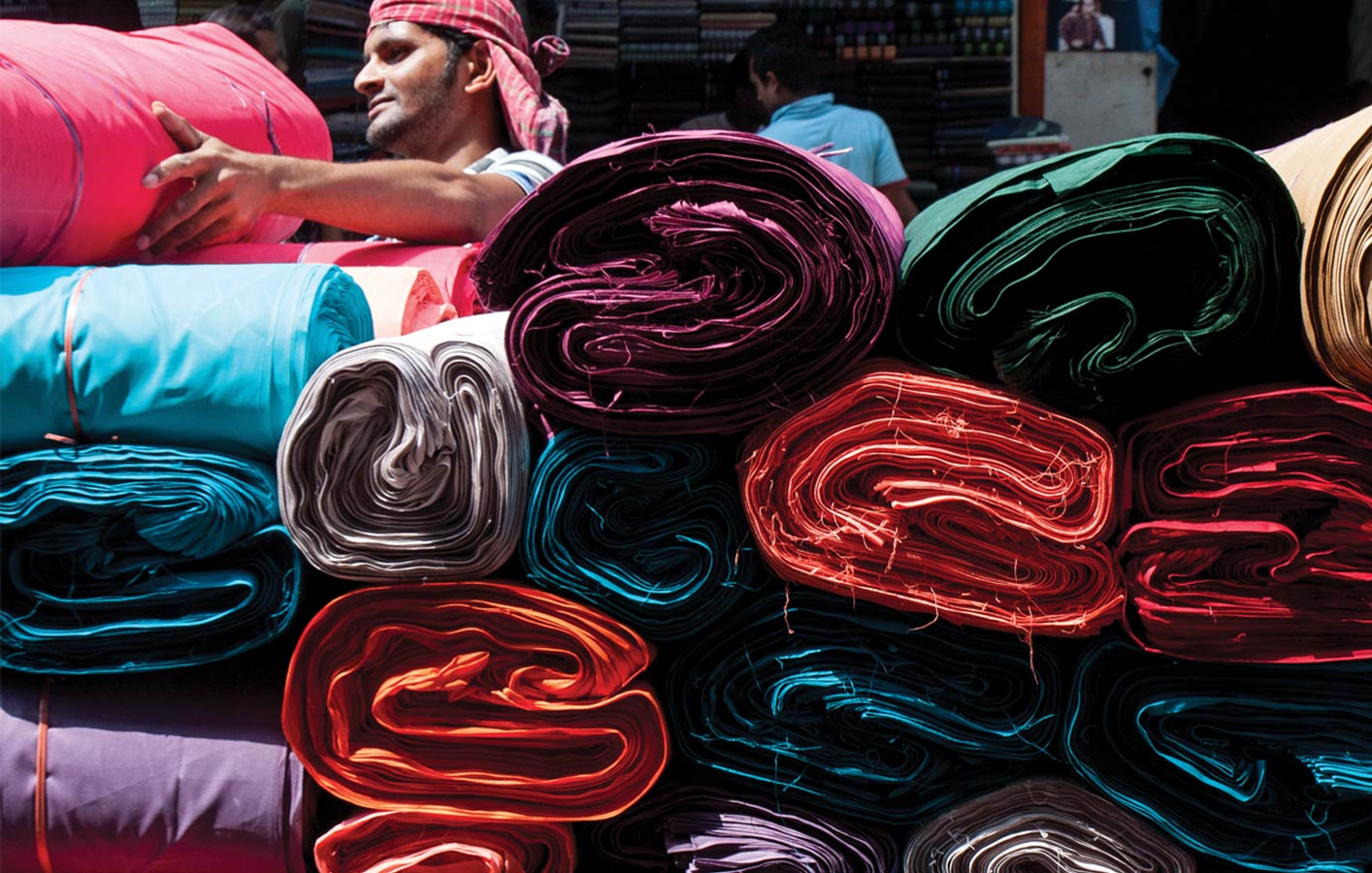 <p>Bolts of fabric for sale in Old Dhaka. A sari starts with nine meters of seamless fabric saturated with color.</p>