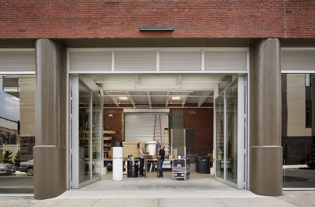 <p>The workshop is enclosed with 13-foot-high operable glass doors that open onto the street to allow full-size mockups and large materials to be moved in and out of the building easily. <br><small>© Michael Moran/OTTO</small></p>