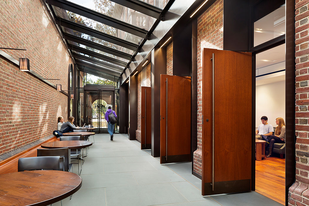 <p>A light court transformed a dark alleyway between a residential hall and dining hall. It is now an active common space in its own right, providing flexible connections among dining hall, seminar rooms, lounge space, and games area.  <br />© Michael Moran / OTTO</p>
