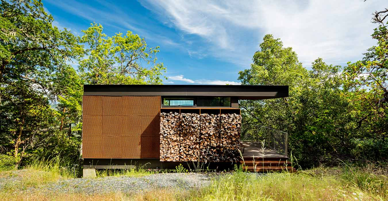 <p>Guest cabins share a the main house's material palette of reclaimed wood, cor-ten steel, floor-to-ceiling glass, and stacked firewood. <br><small>©Tim Griffith</small></p>