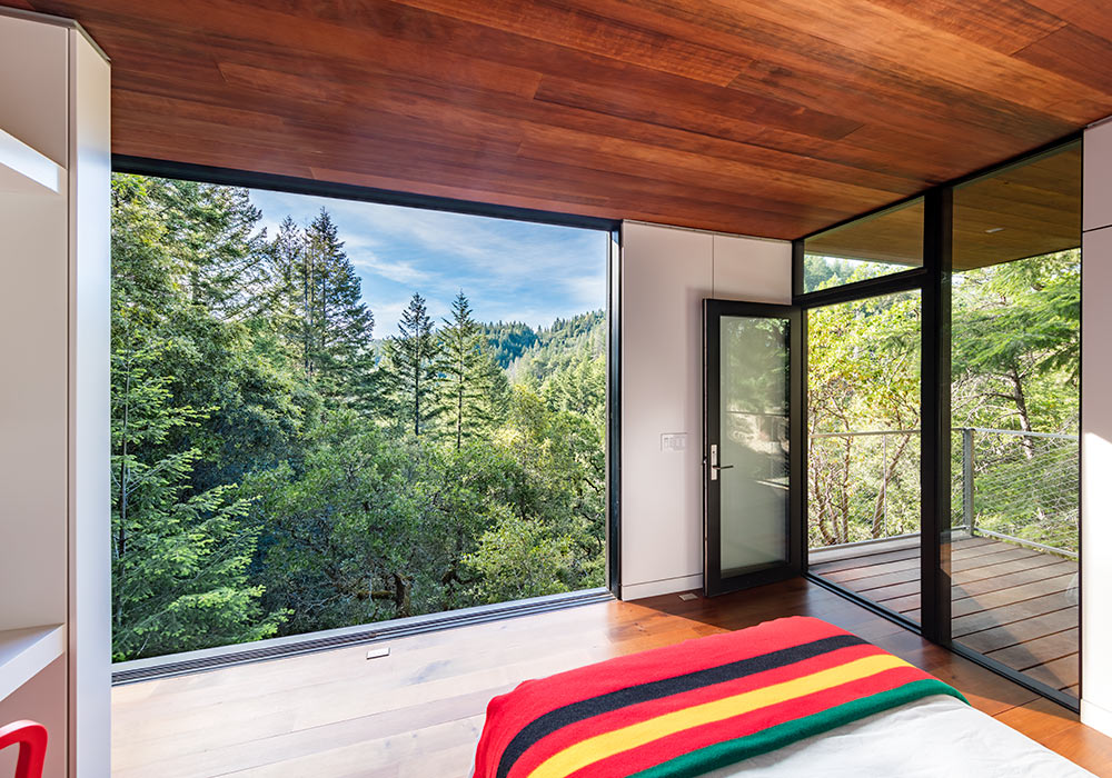 <p>Guest cabins open completely to the outdoors and share the main house's material palette of reclaimed wood, cor-ten steel, and floor-to-ceiling glass. <br><small>&copy;Tim Griffith</small></p>