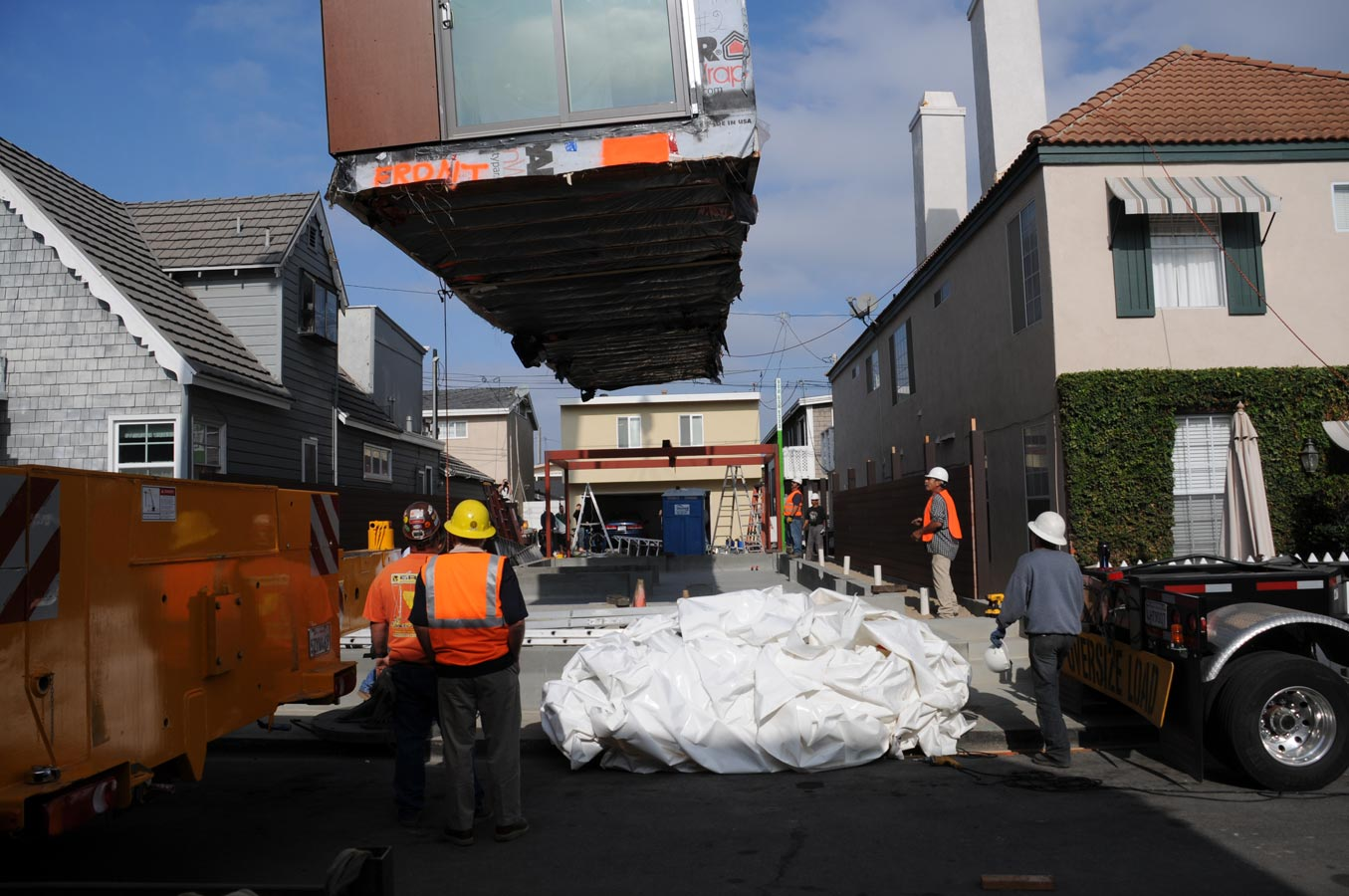 <p>A crane lowers the first of four modules onto a thin lot. Installation was complete in a single day. <br><small>&copy; LivingHomes</small></p>